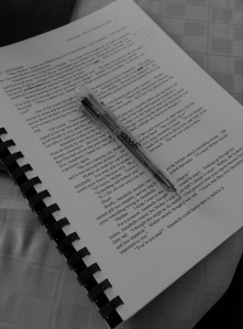 Black and white image of a manuscript with a pen sitting on top